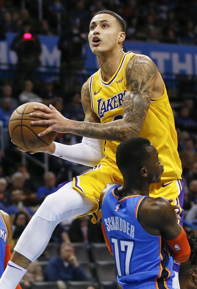 Photo - Los Angeles' Kyle Kuzma (0) takes the ball to the hoop against Oklahoma City's Dennis Schroder (17) in the third quarter during an NBA basketball game between the Los Angeles Lakers and the Oklahoma City Thunder at Chesapeake Energy Arena in Oklahoma City, Thursday, Jan. 17, 2019. Los Angeles won 128-138 in overtime. Photo by Nate Billings, The Oklahoman