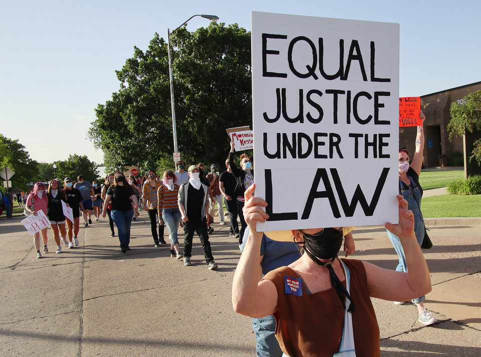 Photo - Jennifer Robertson marches with the Black Lives Matter protesters who want to defund the police march to the Norman City Council chambers in Norman, Tuesday, June 9, 2020. [Doug Hoke/The Oklahoman]