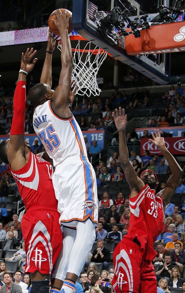 Photo - Oklahoma City's Kevin Durant (35) goes to the basket between Houston's Dwight Howard (12) and Corey Brewer (33) during an NBA basketball game between the Oklahoma City Thunder and the Houston Rockets at Chesapeake Energy Arena in Oklahoma City, Friday, Jan. 29, 2016. Photo by Bryan Terry, The Oklahoman