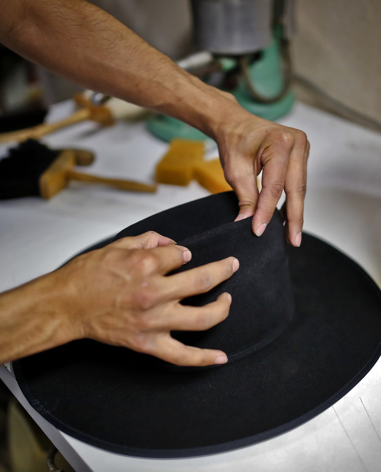 87034567fde Mark Plaza works to shape the crease onto of the hat s crown at Shorty s  Caboy Hattery