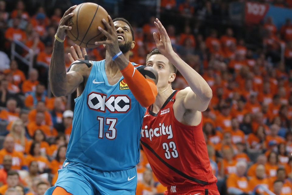 Photo - Oklahoma City's Paul George (13) goes past Portland's Zach Collins (33) during Game 3 in the first round of the NBA playoffs between the Portland Trail Blazers and the Oklahoma City Thunder at Chesapeake Energy Arena in Oklahoma City, Friday, April 19, 2019. Oklahoma City won 120-108. Photo by Bryan Terry, The Oklahoman