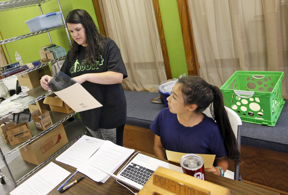 Photo -  Katy Scott and Megon Cheng, 11, organize records where patients check out at the Open Wide Dental Clinic at Portland Avenue Baptist Church. [Photo by Nate Billings, The Oklahoman]