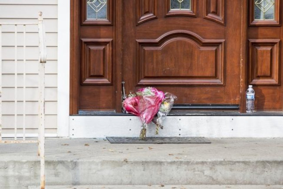 Photo -  Flower bouquets rest on the doorstep of a rabbi's residence in Monsey, N.Y., after a stabbing during a Hanukkah celebration. [Julius Constantine Motal/The Associated Press]