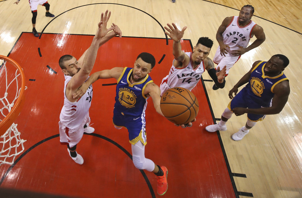 Photo - Golden State Warriors' Stephen Curry (30) drives to the basket between Toronto Raptors' Marc Gasol, left, and Danny Green (14) during Game 1 of basketball's NBA Finals, Thursday, May 30, 2019, in Toronto. (Gregory Shamus/Pool Photo via AP)