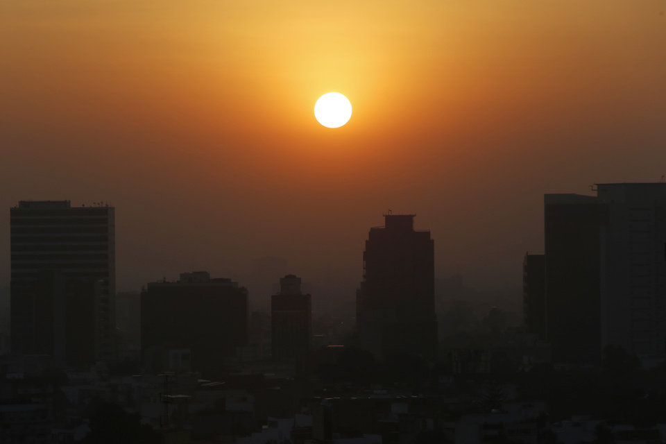 Photo -  In this Feb. 20 photo, the sun rises amid smog during the dry season in Mexico City. [Marco Ugarte/the associated press]