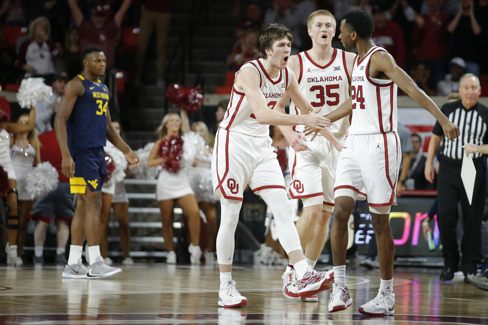 Photo - Oklahoma's Austin Reaves (12), Brady Manek (35) and Jamal Bieniemy (24) celebrate during an NCAA mens college basketball game between the University of Oklahoma Sooners (OU) and the West Virginia Mountaineers at the Lloyd Noble Center in Norman, Okla.,Saturday, Feb. 8, 2020. Oklahoma won 69-59. [Bryan Terry/The Oklahoman]