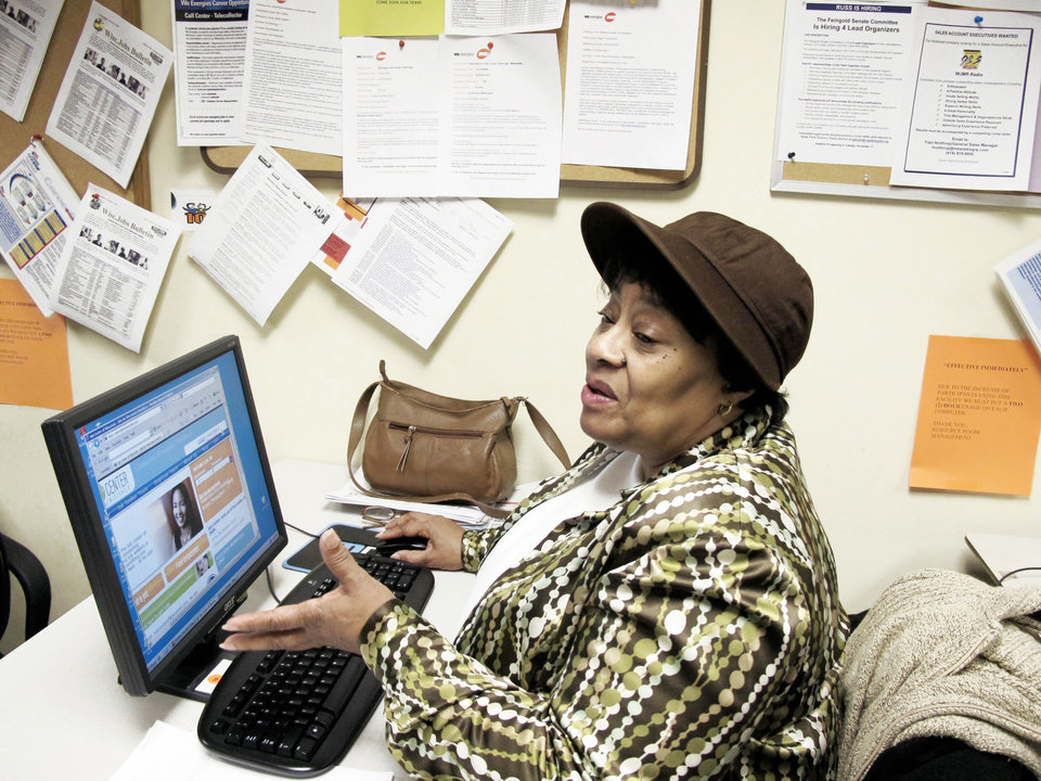 Photo - Carolyn Malone, 62, looks for jobs online at the Milwaukee Hire Center on Friday.  AP Photo