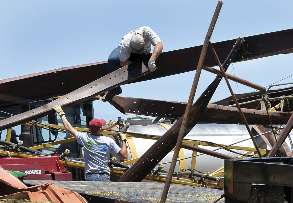 Photo - Two men dismantle pieces of steel that once formed the supports for a large barn south of the El Reno airport  on Saturday, June 1, 2013. The barn was destroyed in last night's tornado in El Reno   Union City..    Photo  by Jim Beckel, The Oklahoman.