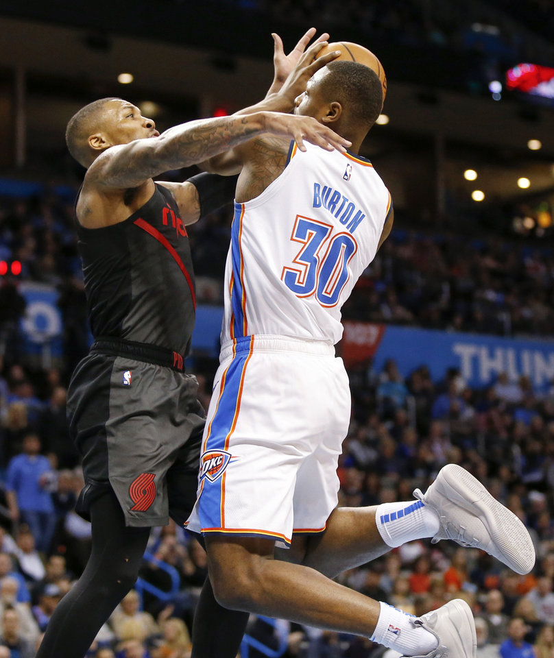 Photo - Oklahoma City's Deonte Burton (30) takes the ball to the basket against Portland's Damian Lillard (0) in the third quarter during an NBA basketball game between the Portland Trail Blazers and the Oklahoma City Thunder at Chesapeake Energy Arena in Oklahoma City, Monday, Feb. 11, 2019. Burton made the shot and was fouled. Oklahoma City won 120-111. Photo by Nate Billings, The Oklahoman