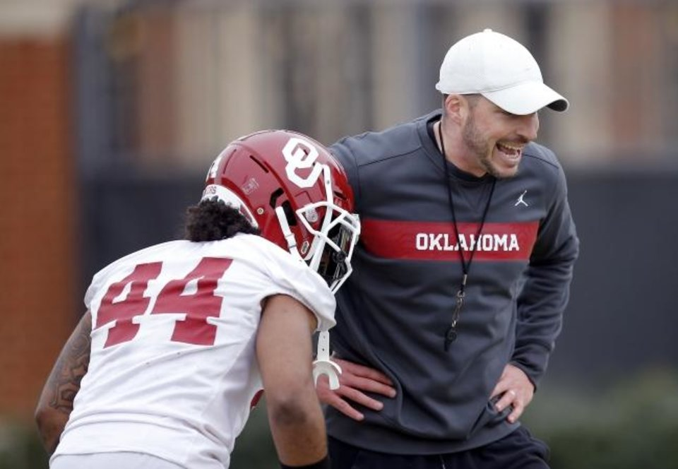 Photo -  OU defensive coordinator Alex Grinch watches Brendan Radley-Hiles line up for a drill on March 7. [Sarah Phipps/The Oklahoman]