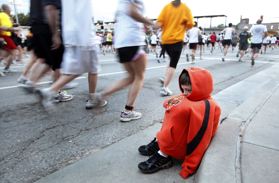 Photo - Jaxon Gregston, 8, of Duncan, Okla. huddles up to stay warm as he watches for his dad Jack to pass by during the tenth anniversary of the 2010 Oklahoma City Memorial Marathon on Sunday, April 25, 2010, in Oklahoma City, Okla.   Photo by Chris Landsberger, The Oklahoman  ORG XMIT: KOD
