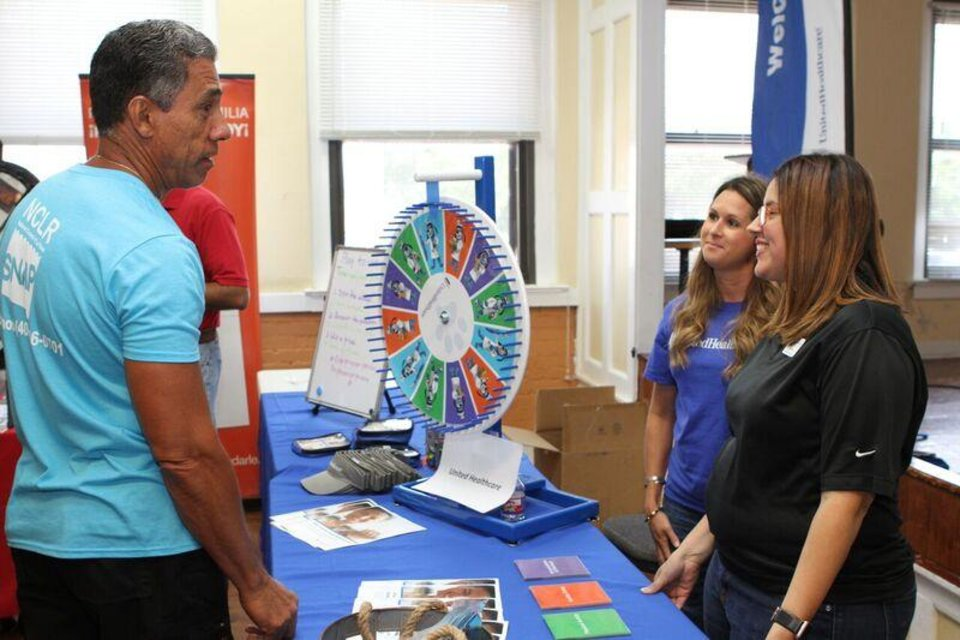 Photo -  Raul Font, president of the Latino Community Development Agency, visits with workers at a health fair. [Photo provided]