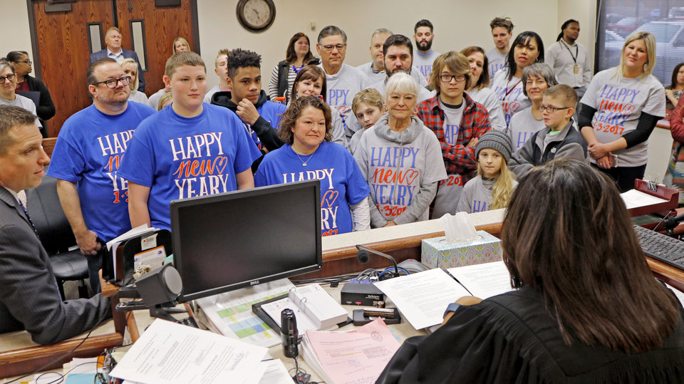 Photo -  Will Yeary, 16, left, stands with his parents, Barbara and Patrick Yeary, and his brother, J.J. Yeary, 17, as his adoption is finalized Tuesday before Judge Cassandra Williams at the Oklahoma Juvenile Justice Center in Oklahoma City. Friends and family members wore