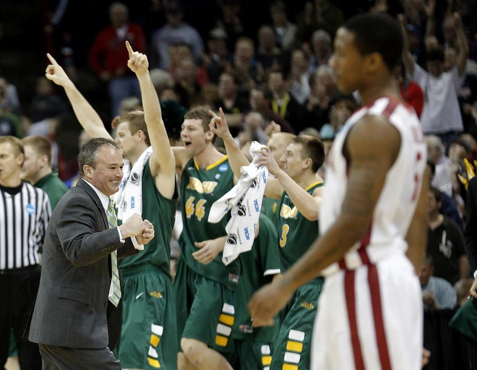 Photo -  North Dakota State head coach Saul Phillips celebrates after beating the Sooner in overtime as Oklahoma's Je'lon Hornbeak (5) walks off the coach during the NCAA men's basketball tournament game in Spokane, Wash., Thursday, March 20, 2014. Oklahoma home lost 80-75. Photo by Sarah Phipps, The Oklahoman