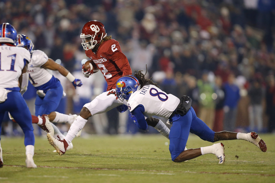 Photo - Oklahoma's CeeDee Lamb (2) leaps past Kansas' Shakial Taylor (8) during a college football game between the University of Oklahoma Sooners (OU) and the Kansas Jayhawks (KU) at Gaylord Family-Oklahoma Memorial Stadium in Norman, Okla., Saturday, Nov. 17, 2018. Photo by Bryan Terry, The Oklahoman