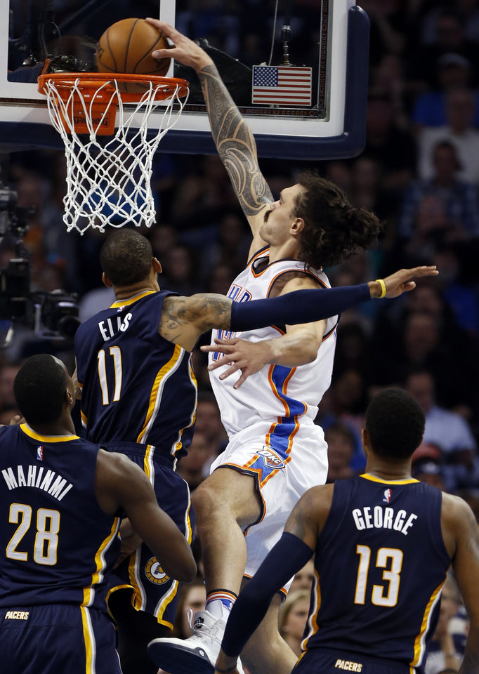 Photo - Oklahoma City Thunder's Steven Adams (12) scores guarded by Indiana's Monta Ellis (11) in the first half of an NBA basketball game where the Oklahoma City Thunder play the Indiana Pacers at the Chesapeake Energy Arena in Oklahoma City, on Feb. 19, 2016.  Photo by Steve Sisney The Oklahoman