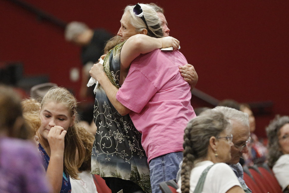 Photo -  Mourners hug Friday during the funeral of Ronald and Kay Wilkson in Luther. [Photo by Chris Landsberger, The Oklahoman]