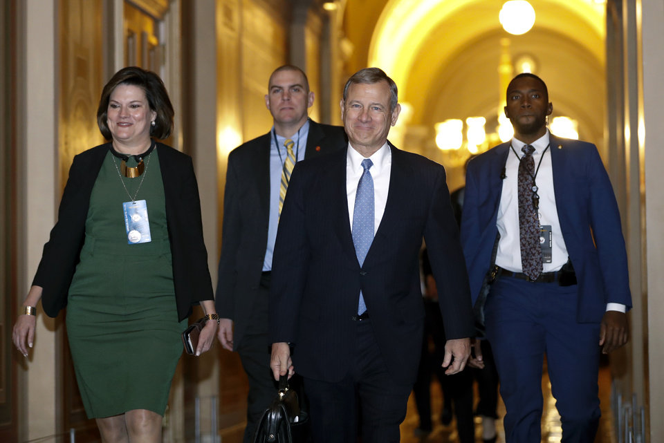Photo -  Supreme Court Chief Justice John Roberts, second from right, arrives at the U.S. Capitol in Washington on Thursday.