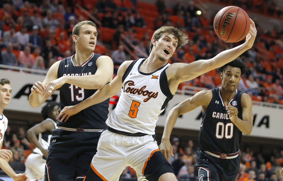 Photo - Oklahoma State's Duncan Demuth (5) reaches for the ball between South Carolina's Felipe Haase (13) and A.J. Lawson (00) during a NCAA basketball game between the Oklahoma State Cowboys (OSU) and the University of South Carolina at Gallagher-Iba Arena in Stillwater, Okla., Saturday, Jan. 26, 2019. Photo by Bryan Terry, The Oklahoman