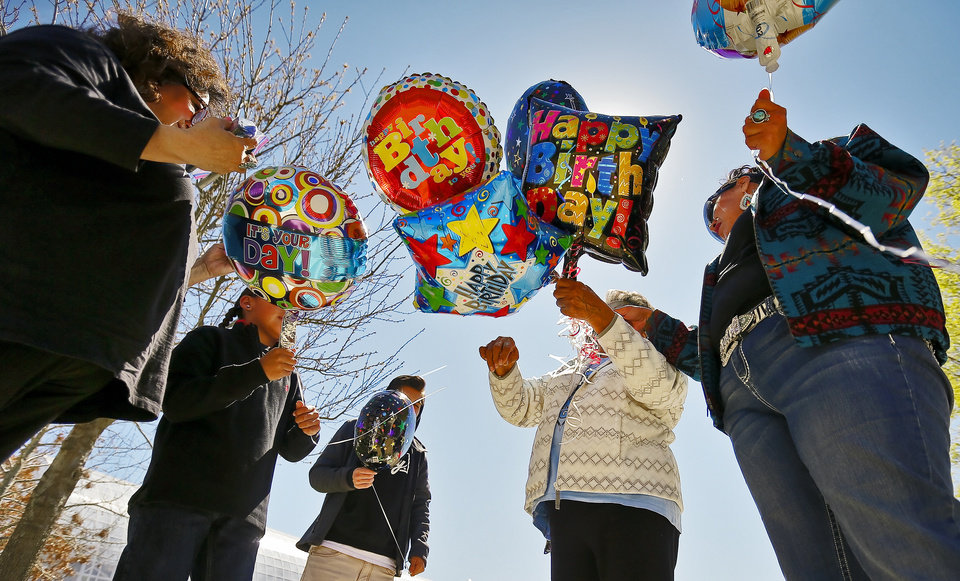 Photo - The Wahnee family picks out a balloon to write a message on as they prepares to release the balloon in honor of Bradley Wahnee, who was killed in 2009 during a drive by shooting, to mark his birthday at the Myriad Botanical Gardens in Oklahoma City, Okla. on Monday, March 21, 2016. The family releases balloons every year on Bradley's birthday and the date he was killed.  Photo by Chris Landsberger, The Oklahoman