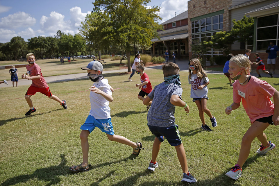 Photo - Children play a game outside Henderson Hills Baptist Church in Edmond, Okla., Wednesday, Aug. 26, 2020. The church has begun offering Edmond school students a place to go on Wednesdays to get homework help, use the free wi-fi for virtual learning, free lunch and other activities. [Bryan Terry/The Oklahoman]