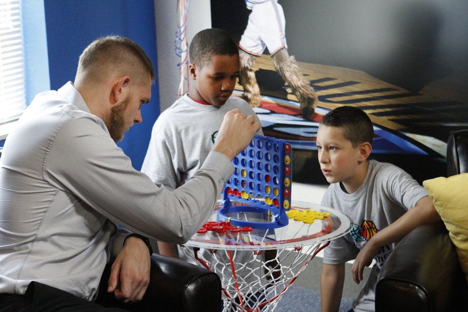 Photo - Oklahoma City Thunder's Cole Aldrich, left plays Connect 4 with Jaquay Wisby, 12, and Xavier Espinoza, 11, at the opening of the NBA Cares Learn & Play Center at the City Rescue Mission in Oklahoma City. Photo By Steve Gooch, The Oklahoman  Steve Gooch - The Oklahoman