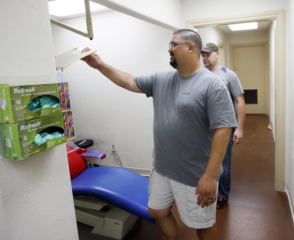 Photo -  Tony Mullican, co-director of Portland Avenue Baptist Church's Open Wide Dental Clinic, leads patient John Nelson into the treatment area at the church, 1301 N Portland Ave. [Photo by Nate Billings, The Oklahoman]