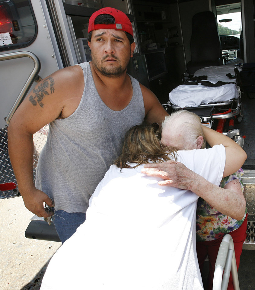 Photo - Margaret Free is embraced by family members after being rescued from rising flood waters on Sunday, August 19, 2007, in Kingfisher, Okla. By James Plumlee, The Oklahoman.