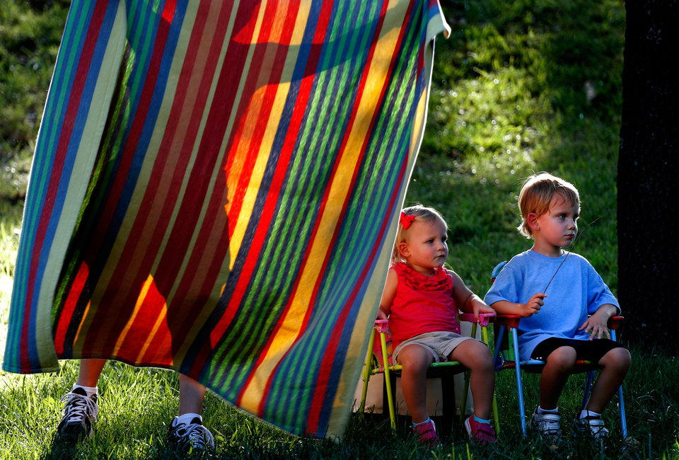 Photo -  Katie Peters, 2, and her brother Will, 4, take a seat as their mother, Elizabeth Peters, spreads out a blanket before watching Mike Black & The Stingrays perform during Edmond Parks and Recreation Department's concert series at E.C. Hafer Park in Edmond, Okla., Thursday, July 11, 2013. Photo by Bryan Terry, The Oklahoman