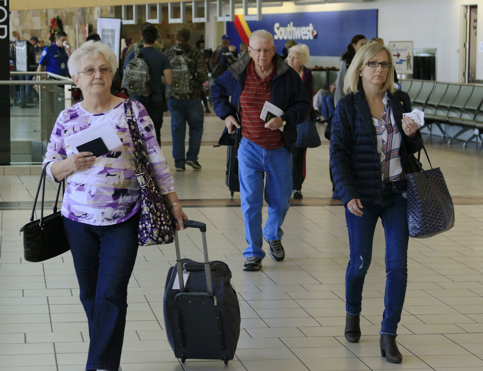 Photo -  Travelers walk through Will Rogers World Airport on Monday in Oklahoma City during the beginning of the Thanksgiving travel season. [Photo by Paul Hellstern, The Oklahoman]