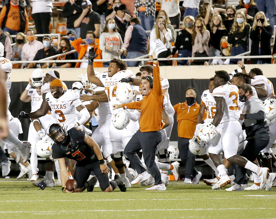Photo - Texas celebrates as Oklahoma State's Spencer Sanders (3) reacts after being sacked in overtime in during the college football game between the Oklahoma State University Cowboys and the University of Texas Longhorns at Boone Pickens Stadium in Stillwater, Okla., Saturday, Oct. 31, 2020. Texas won 41-34. Photo by Sarah Phipps, The Oklahoman
