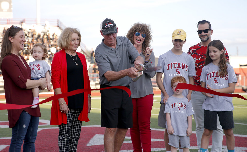 Photo - Gary Rose cuts the ribbon for Gary Rose Stadium before the high school football game between Carl Albert and Del City at Carl Albert High School in Midwest City, Okla., Friday, Sept. 13, 2019. [Sarah Phipps/The Oklahoman]