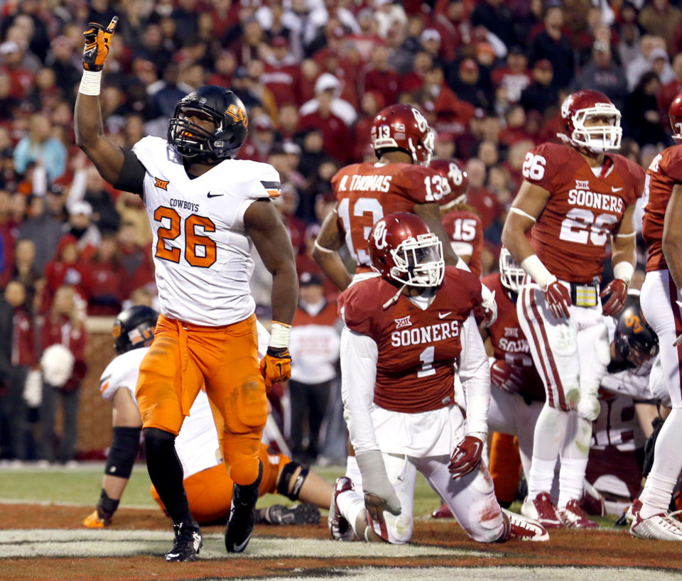 Photo - Oklahoma State's Desmond Roland (26) celebrates a touchdown in the fourth quarter during the Bedlam college football game between the University of Oklahoma Sooners (OU) and the Oklahoma State Cowboys (OSU) at Gaylord Family-Oklahoma Memorial Stadium in Norman, Okla., Saturday, Dec. 6, 2014. Photo by Sarah Phipps, The Oklahoman