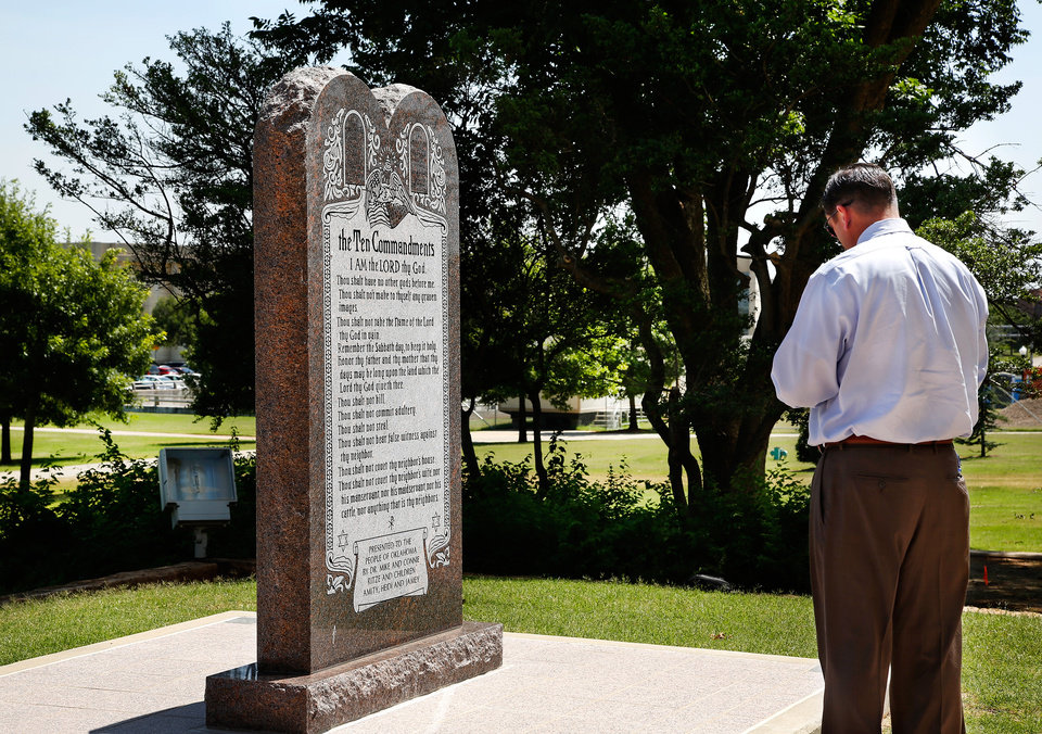 Photo - A man pauses for about four minutes in front of the Ten Commandments monument Tuesday. Before walking away, he said in hushed tones,