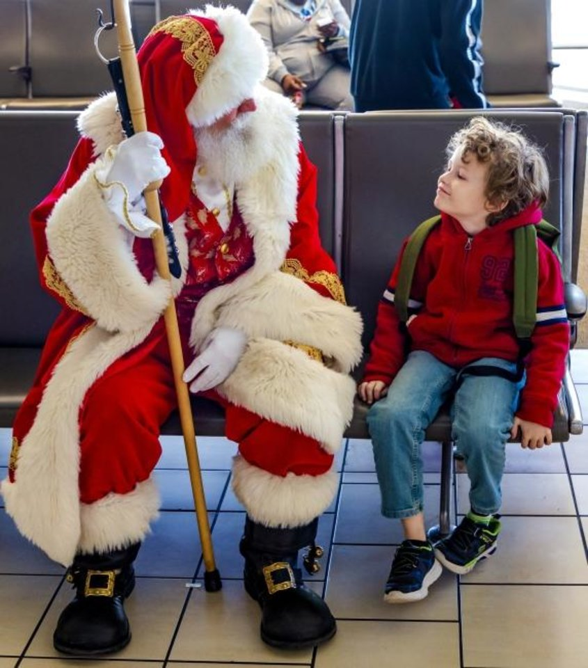 Photo -  Santa Claus visits with Devlin Gonzalez, 8, of Altus, as he waits to catch a flight Thursday at Will Rogers World Airport in Oklahoma City. [Chris Landsberger/The Oklahoman]