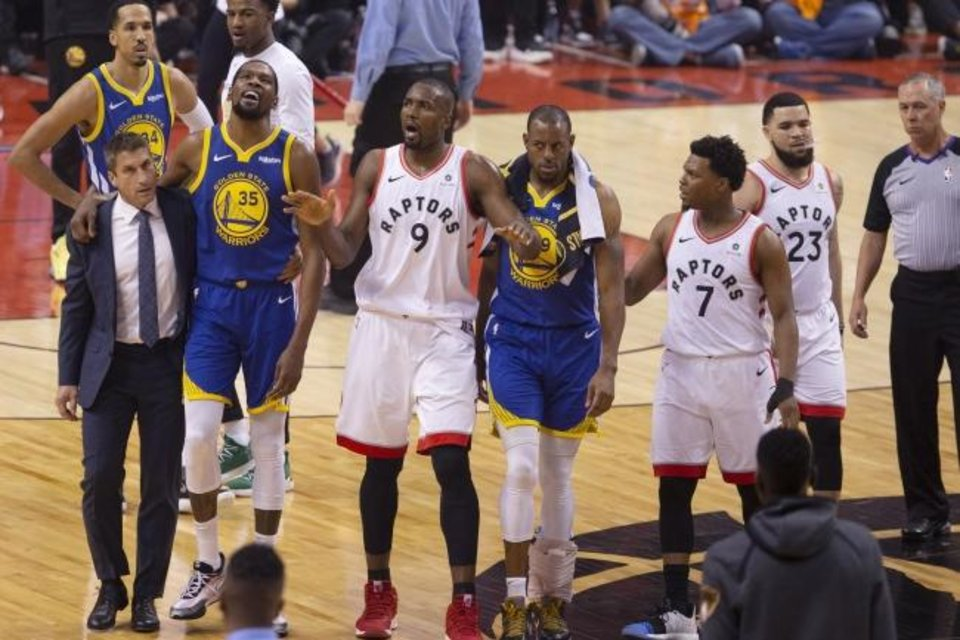 Photo -  Golden State's Kevin Durant (35) is helped off the court Monday night after suffering an Achilles injury in the Warriors' 106-105 Game 5 win. Toronto's Serge Ibaka (9), Durant's former teammate with the Thunder, implores the crowd to stop cheering the injury. [Chris Young/The Canadian Press via AP]