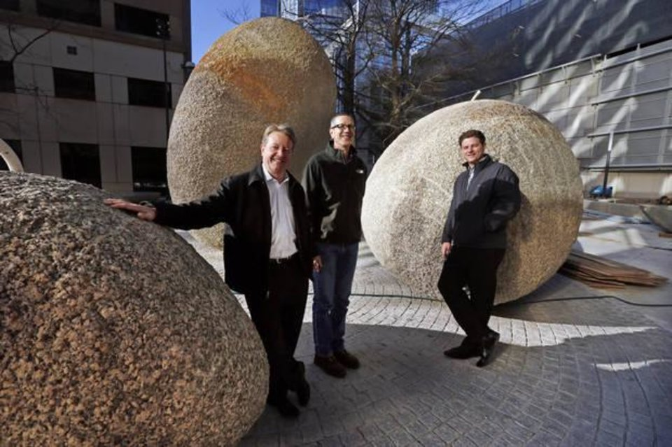Photo -  Mike Clark, center, senior project manager for Oklahoma City's Public Works Department, and landscape architects Scott Howard and Nick Fairless, show off huge rocks that are part of the downtown Pedestrian Plaza project Friday in Oklahoma City. [Photos by Steve Sisney, The Oklahoman]