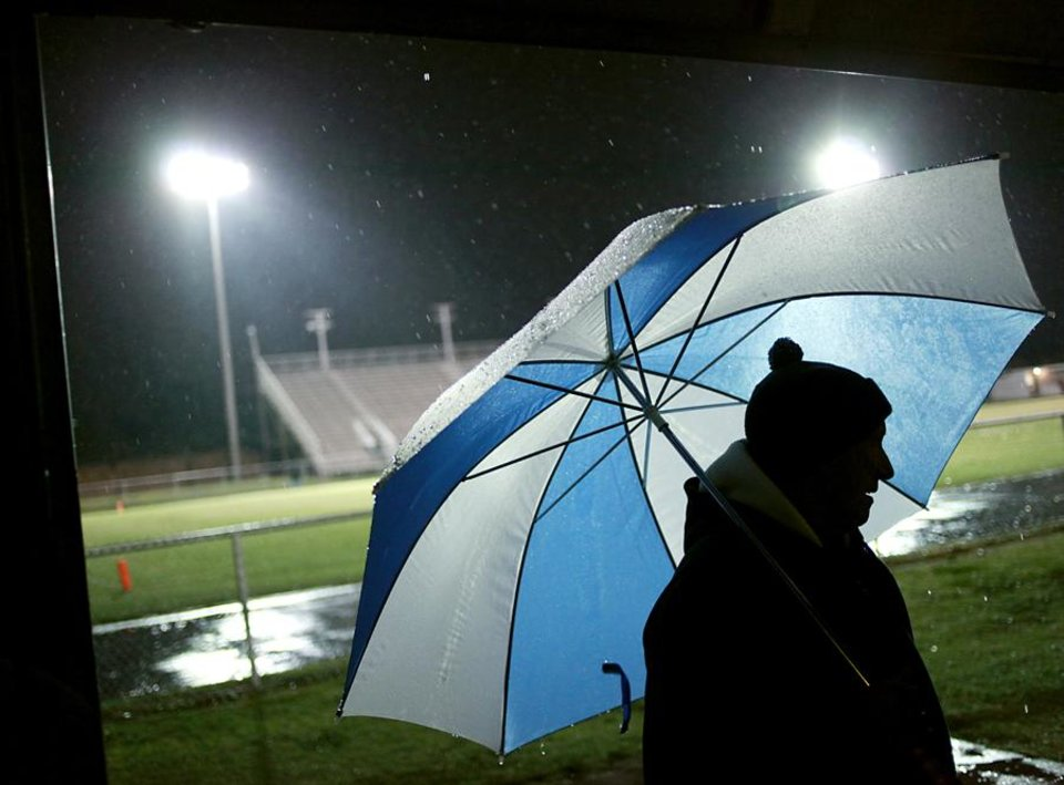 Photo -  Ron Millican stands under an umbrella near the door of the maintenance barn at C.B. Speegle Stadium in Oklahoma City before the high school football game between Del City and U.S. Grant on Thursday, Oct. 27, 2011. Photo by John Clanton, The Oklahoman