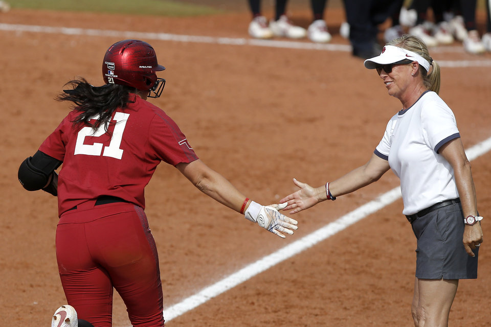Photo - Oklahoma coach Patty Gasso slaps hands with Oklahoma's Grace Green (21) as she runs home after hitting a home run in the fifth inning of the second softball game in the Norman Super Regional between the University of Oklahoma (OU) and Northwestern in Norman, Okla., Saturday, May 25, 2019. Oklahoma won 8-0 to send them to the Women's College World Series. [Bryan Terry/The Oklahoman]