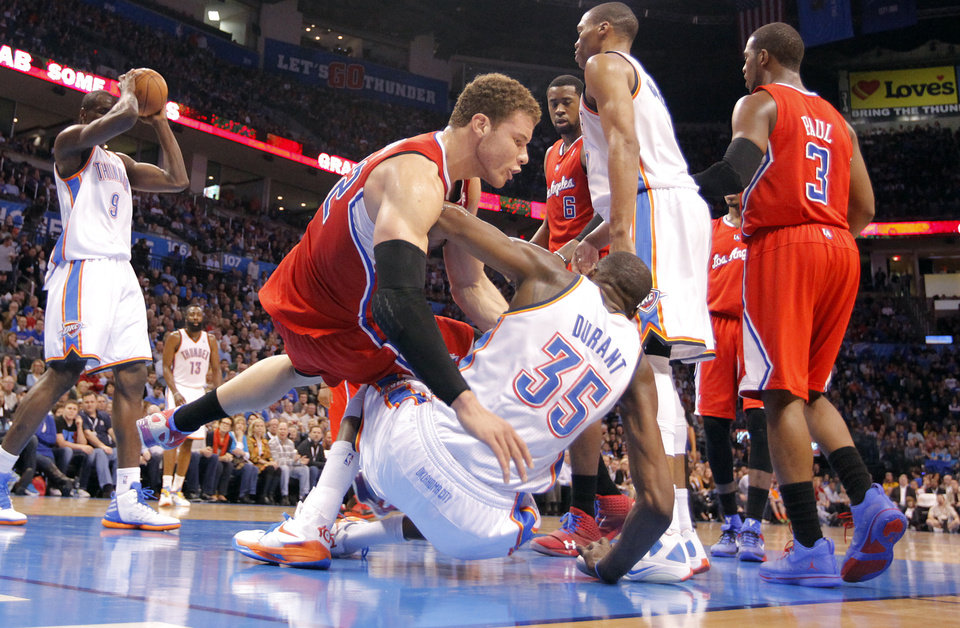 Photo - Los Angeles Clippers power forward Blake Griffin (32) and Oklahoma City Thunder small forward Kevin Durant (35) fall to the floor on a play during the NBA basketball game between the Oklahoma City Thunder and the Los Angeles Clippers at Chesapeake Energy Arena on Wednesday, March 21, 2012 in Oklahoma City, Okla.  Photo by Chris Landsberger, The Oklahoman