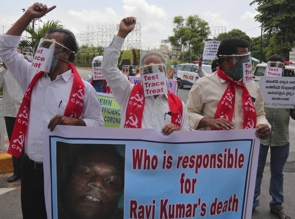 Photo -  Activists of Communist Party of India Marxist display placards on face shields and shout slogans during a protest asking the state government to increase testing and free treatment for all COVID-19 patients in Hyderabad, India, Monday, June 29, 2020. Governments are stepping up testing and warily considering their next moves as the number of newly confirmed coronavirus cases surges in many countries. India reported more than 20,000 new infections on Monday. (AP Photo/Mahesh Kumar A.)