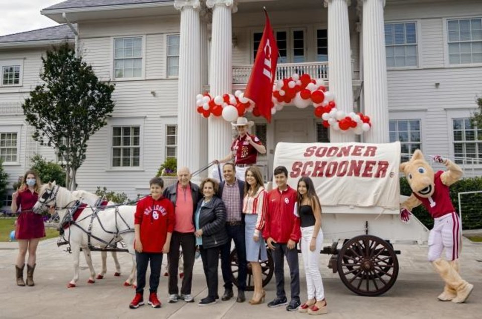 Photo -  From left: Camille Fichera, Jude Harroz, Dr. Joseph Harroz Sr., Mary Ann Harroz, OU president Joseph Harroz Jr., Ashley Tate, Joseph Harroz, Zara Harroz and Boomer pose for a photo May 18. Driving the Sooner Schooner was Robert Riley. [CHRIS LANDSBERGER/THE OKLAHOMAN]