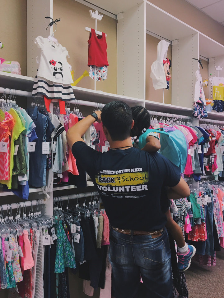 Photo -  A volunteer helps a child choose items at the Back2School shop offered by Citizens Caring for Children and Oklahoma United Methodist Circle of Care. [Photo provided]