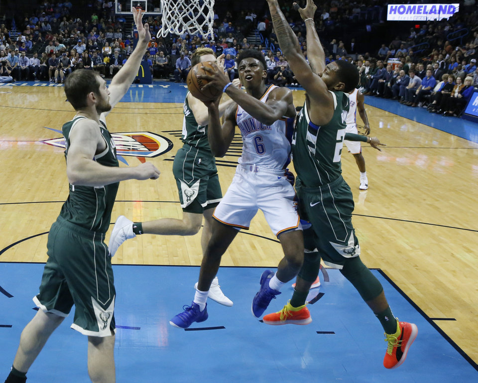 Photo -  Oklahoma City Thunder guard Hamidou Diallo (6) shoots between Milwaukee Bucks center Tyler Zeller, left, and guard Sterling Brown, right, in the fourth quarter of an NBA preseason basketball game in Oklahoma City, Tuesday, Oct. 9, 2018. (AP Photo/Sue Ogrocki)