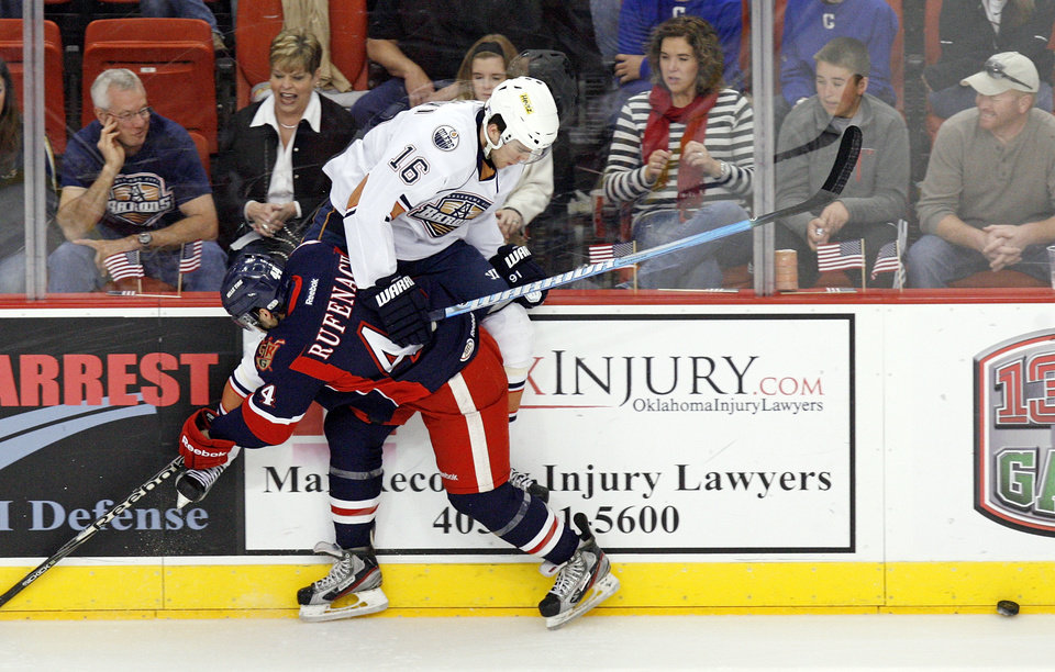 Photo - Grand Rapids' Bryan Rufenach (44) checks Oklahoma City's Magnus Paajarvi (16) into the boards during an AHL hockey game between the Oklahoma City Barons and the Grand Rapids Griffins at the Cox Convention Center in Oklahoma City, Saturday, March 24, 2012. Photo by Nate Billings, The Oklahoman