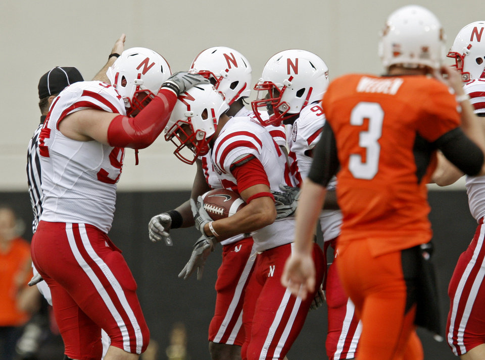 Photo - Nebraska's Eric Hagg, center, celebrates with Jared Crick, left, P.J. Smith and Jason Ankrah as OSU's Brandon Weeden walks away after an interception during the college football game between the Oklahoma State Cowboys (OSU) and the Nebraska Huskers (NU) at Boone Pickens Stadium in Stillwater, Okla., Saturday, Oct. 23, 2010. Photo by Bryan Terry, The Oklahoman