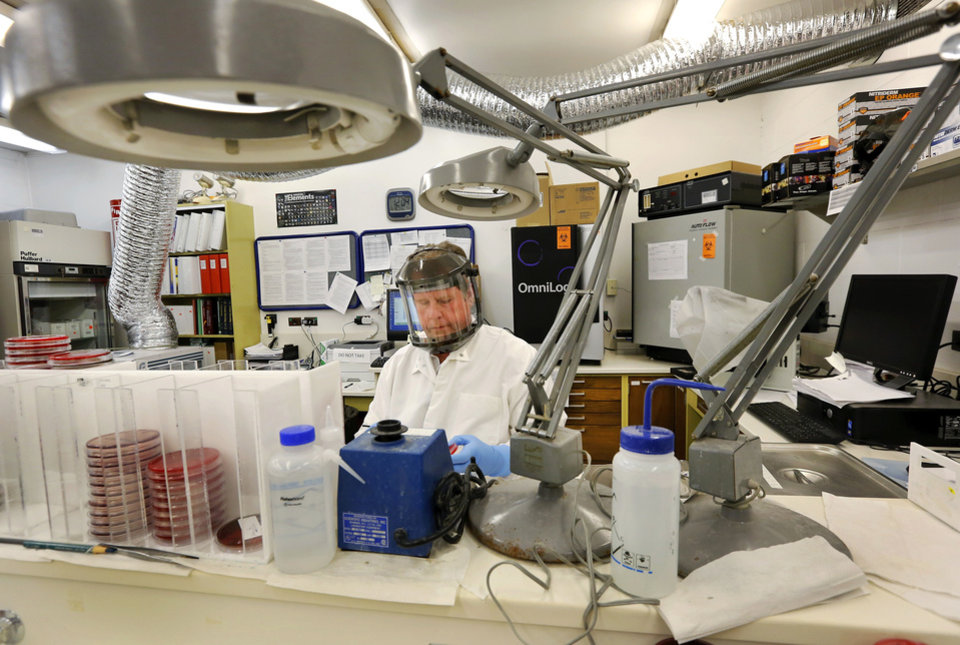 Photo - Mike Lytle, laboratory bioterrorism coordinator and supervisor for microbiology, is shown at his work station  in the public health laboratory on Thursday, Jan. 16, 2014.  The Oklahoma public health laboratory is located in the Oklahoma State Department of Health building in Oklahoma City. Public health officials say they are out of room to expand the lab and could lose lab accreditation if they aren't able to build a new lab soon. Losing accreditation would mean the lab's scientists could not perform thousands of tests for county health departments and hospitals across the state.   Photo by Jim Beckel, The Oklahoman