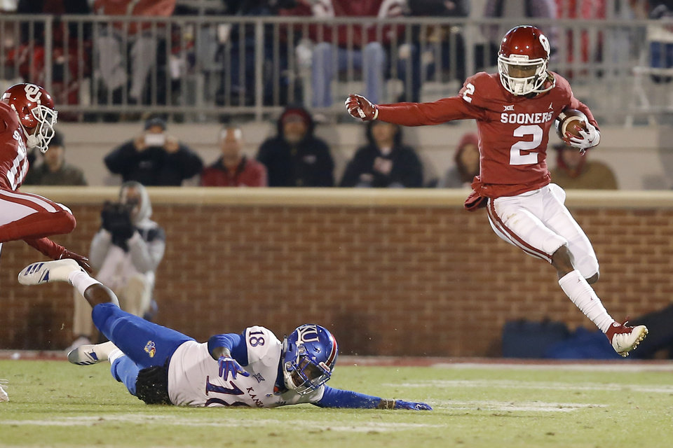 Photo - Oklahoma's CeeDee Lamb (2) leaps past Kansas' Denzel Feaster (18) as he returns a punt during a college football game between the University of Oklahoma Sooners (OU) and the Kansas Jayhawks (KU) at Gaylord Family-Oklahoma Memorial Stadium in Norman, Okla., Saturday, Nov. 17, 2018. Photo by Bryan Terry, The Oklahoman