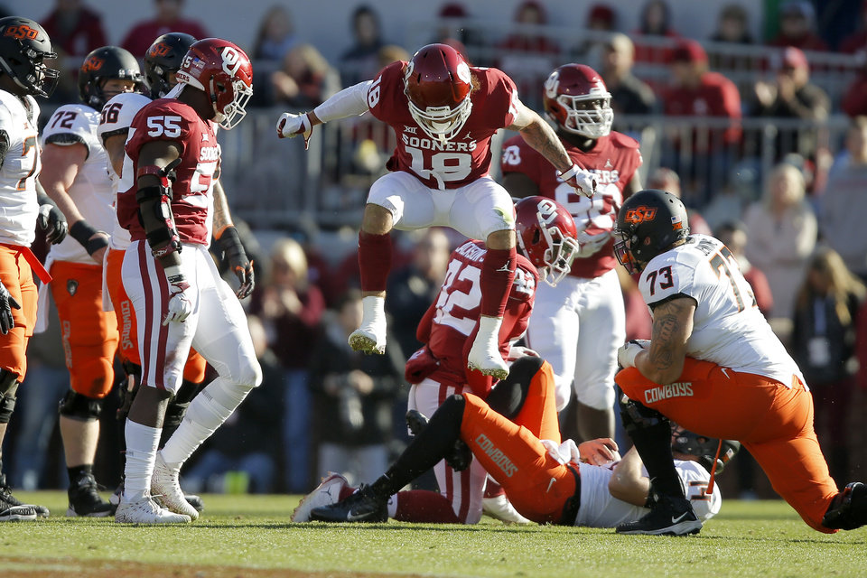 Photo - Oklahoma's Curtis Bolton (18) celebrates after Oklahoma State's Taylor Cornelius (14) was brought down for a loss during a Bedlam college football game between the University of Oklahoma Sooners (OU) and the Oklahoma State University Cowboys (OSU) at Gaylord Family-Oklahoma Memorial Stadium in Norman, Okla., Nov. 10, 2018.  Photo by Bryan Terry, The Oklahoman