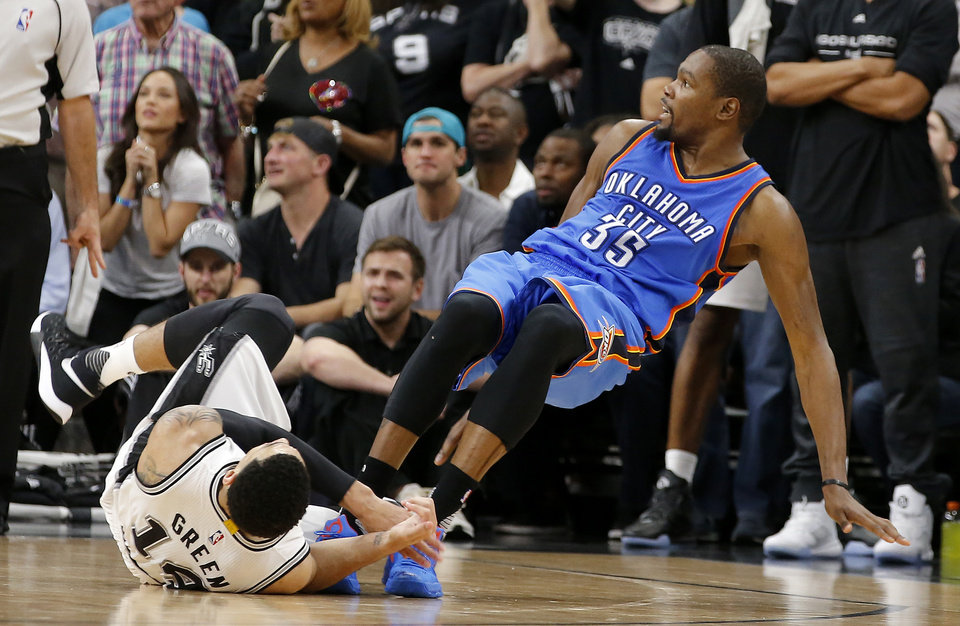 Photo - Oklahoma City's Kevin Durant (35) falls down as San Antonio's Danny Green (14) is called for a foul in the final minute of Game 5 of the second-round series between the Oklahoma City Thunder and the San Antonio Spurs in the NBA playoffs at the AT&T Center in San Antonio, Tuesday, May 10, 2016. Oklahoma City won 95-91. Photo by Bryan Terry, The Oklahoman